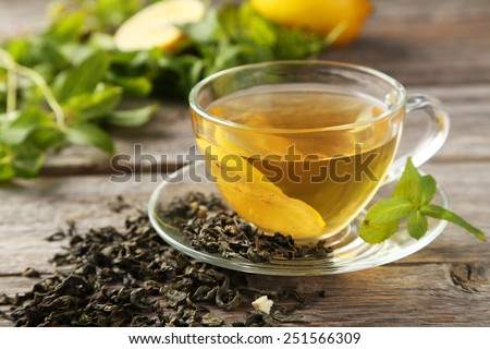 Cup with green tea on grey wooden background - stock photo