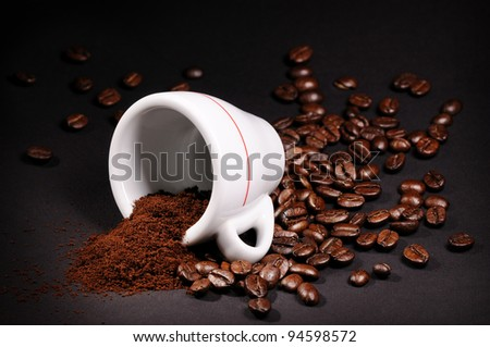 Cup with heap of coffee beans on black background - stock photo