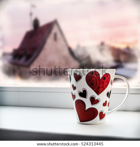 cup with heart on the window sill on the background of a winter city. It can be used for Valentine's Day greetings