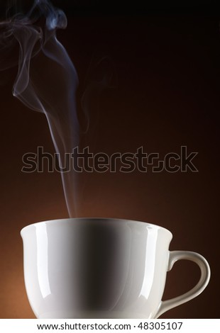 Cup with hot beverage on brown background - stock photo