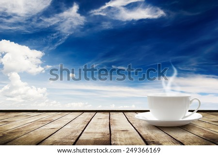 Cup with hot drink on table over beautiful sky background - stock photo