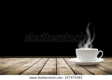 Cup with hot drink on table over black background - stock photo