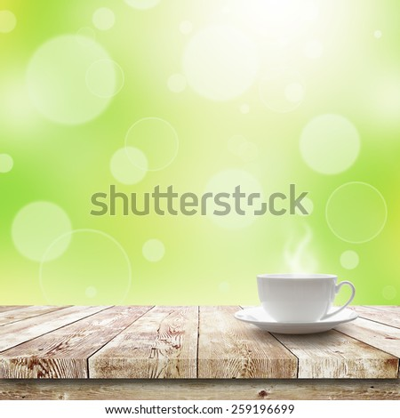 Cup with hot drink on table over Green bokeh and sunlight. Beauty morning breakfast background - stock photo