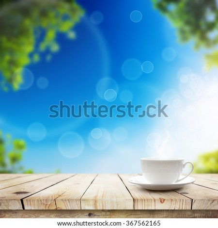 Cup with hot drink on table over Green bokeh and sunlight. Beauty morning breakfast spring background - stock photo