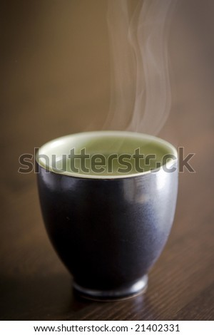 Cup with hot water and steam coming out of it - stock photo