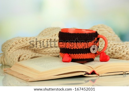 Cup with knitted thing on it and open book close up - stock photo