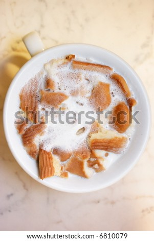 Cup with milk and biscuits, soaked in it, on a marble surface. Pastel tone. View from above. Shallow depth of field.