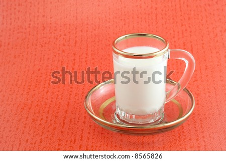 Cup with milk. The cup stands on saucer. Object over red background.