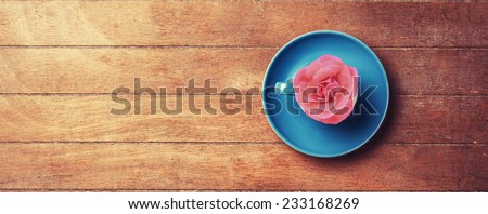 Cup with rose insode. On wooden table. - stock photo
