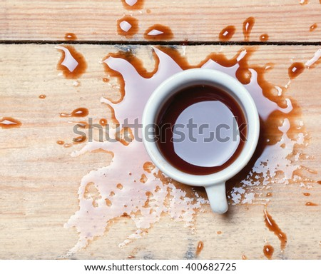 cup with spilled coffee on a wooden surface.toned.view from above - stock photo