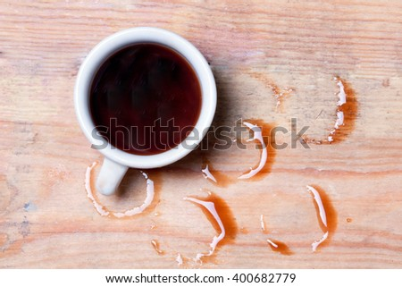 cup with spilled coffee on a wooden surface.view from above - stock photo