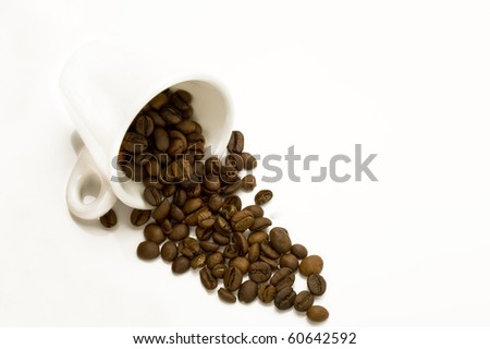 Cup with spilt coffee beans isolated on white - stock photo