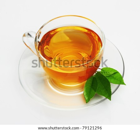 Cup with tea and green leaf on white - stock photo