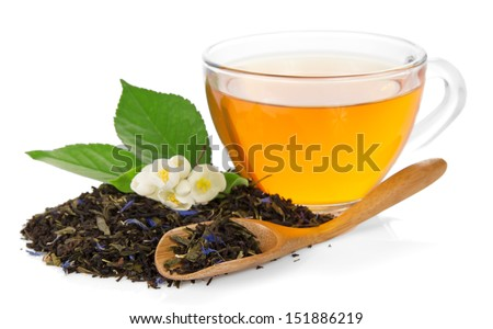 Cup with tea, tea leaves with cornflowers, a flower of a jasmine and a wooden spoon isolated on white