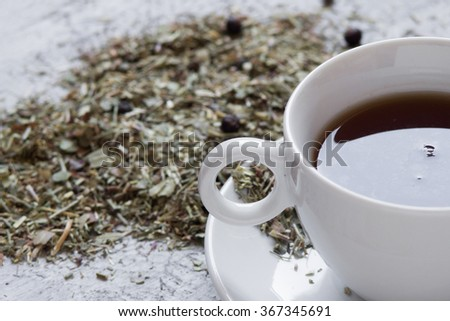 Cup with tea with dry herbs on wooden background