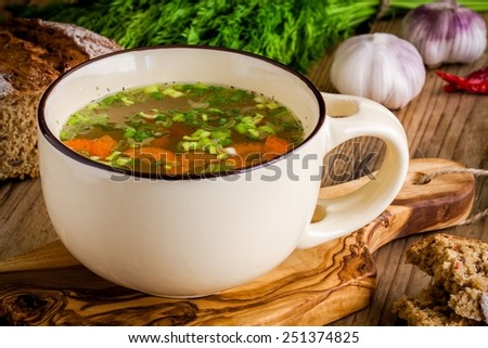cup with vegetable soup on a rustic wooden background