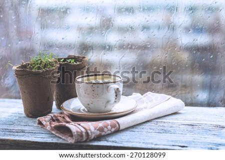 Cup with warm drink on wooden table in front of window with rain drops, rainy weather. Moody still life. Cold pale tones, horizontal image - stock photo