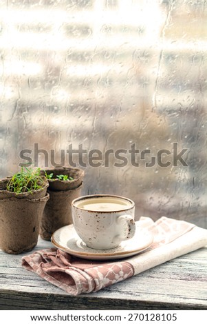 Cup with warm drink on wooden table in front of window with rain drops, rainy weather. Moody still life. Warm tones, vertical image - stock photo