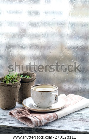 Cup with warm drink on wooden table in front of window with rain drops, rainy weather. Moody still life - stock photo