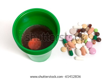 cup with water and heap of pills on white - stock photo