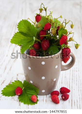 Cup with wild strawberry on a wooden background