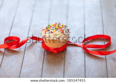 Cupcake and bow on wooden table. - stock photo
