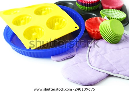 Cupcake cases with kitchen gloves and potholder and silicone mould on white background - stock photo