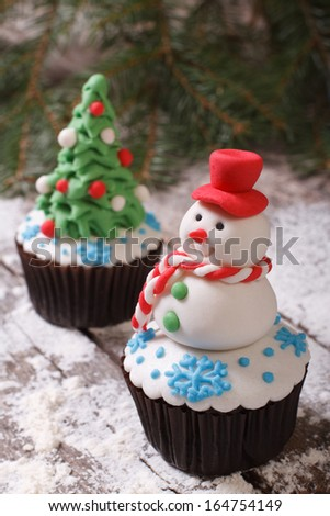 Cupcake Christmas snowman on the background of fir trees - stock photo