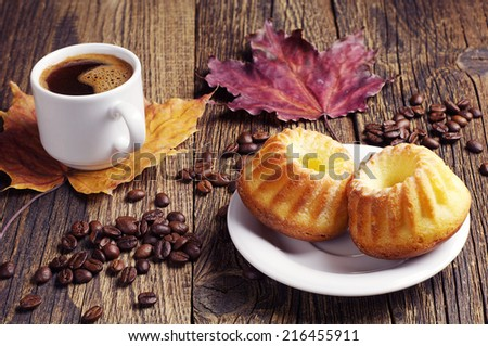 Cupcake, cup of hot coffee and autumn leaves on wooden background
