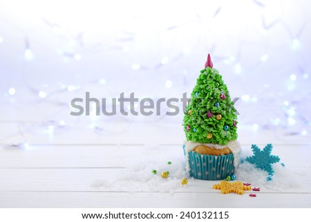 Cupcake decorated with Christmas tree on the Christmas lights background. - stock photo