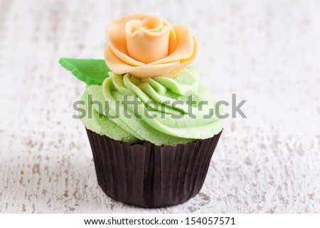cupcake decorated with mint buttercream and flower