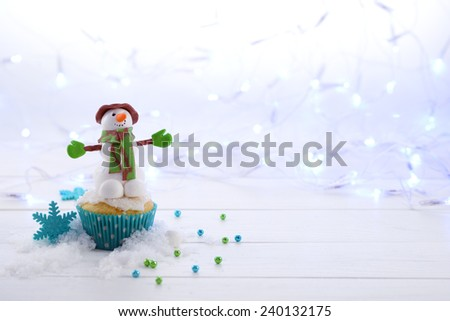 Cupcake decorated with sugar Snowman on the Christmas lights background horizontal format. - stock photo