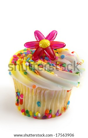 Cupcake decorated with white icing, sprinkles and plastic flower  decorations. - stock photo