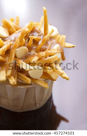 cupcake in a white paper cup decorated to look like a poutine