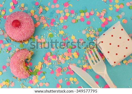 Cupcake, knife, fork and gift box on blue confetti background - happy birthday card - stock photo