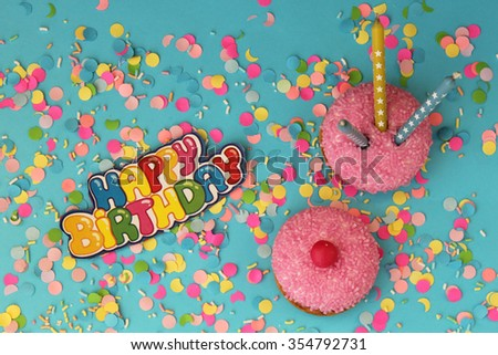 Cupcake on blue confetti background - happy birthday card - stock photo