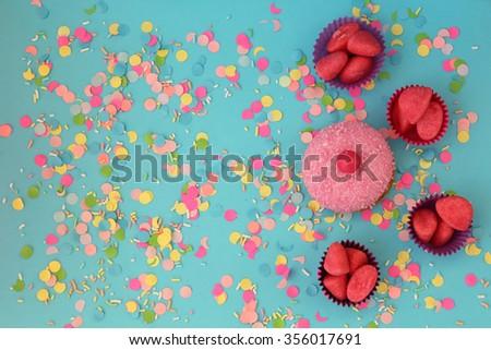 Cupcake on blue confetti background - happy birthday card - stock photo