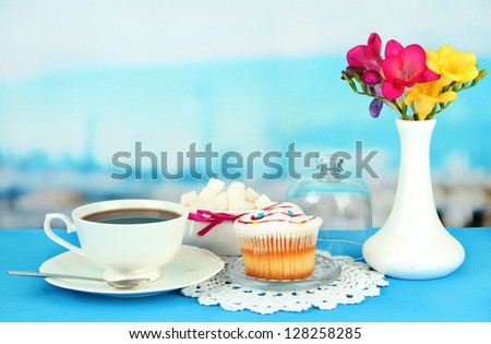 Cupcake on saucer with glass cover, on bright background - stock photo