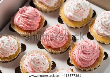 Cupcake packaging, delivery box, vanilla cupcakes with pink and white cream,top view, selective focus, close up - stock photo