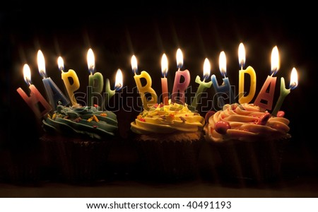 cupcake shot on a black background with happy birthday candles - stock photo
