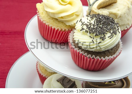 Cupcake stand  on red tablecloth - stock photo