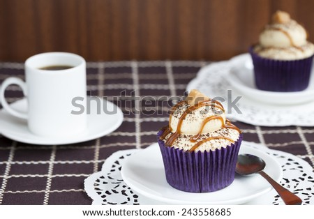 Cupcake  topped with cappuccino flavored frosting and decorated with caramel, cocoa powder and vanilla fudge - stock photo