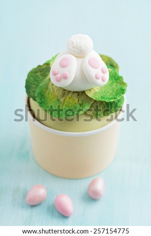 Cupcake with a fondant Easter bunny topper. Bunny is digging in fondant salad with his butt and feet sticking out - stock photo