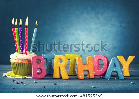 Cupcake with birthday candles on a blue background