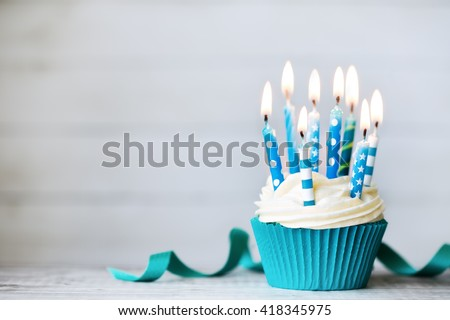 Cupcake with blue birthday candles - stock photo