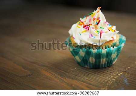 Cupcake with candies in a checkered paper on a wooden table