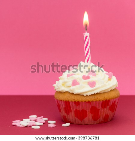 cupcake with candle and pink background - stock photo