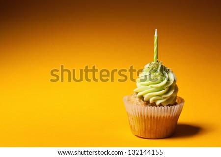 cupcake with candle isolated on orange background - stock photo