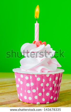 Cupcake with candle on top on color background