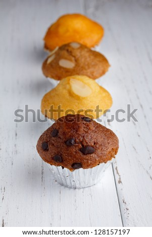 Cupcake with chocolate chips, almond and butter on wooden table